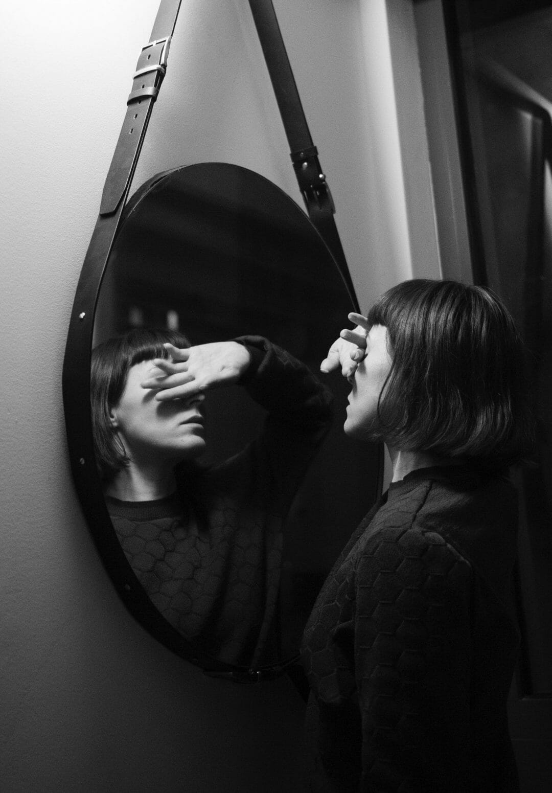 black and white photo of woman covering face while standing in front of mirror